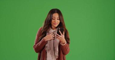 Beautiful female Latina using smartphone on green screen