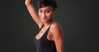 Sexy woman in tight black dress dancing on grey background