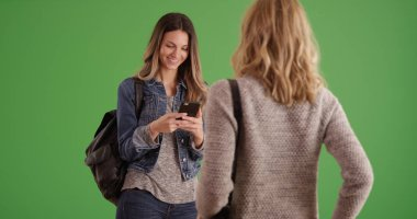 Attractive brunette about to take picture of friend with phone on green screen