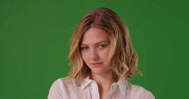 White female dressed in white button shirt looking at camera on green screen