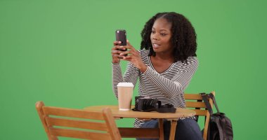 African American woman taking photo with phone at cafe on green screen