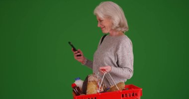 Happy old woman texting on phone while shopping for groceries on green screen