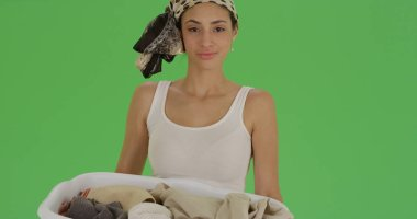 Latina poses for portrait holding a laundry basket on green screen