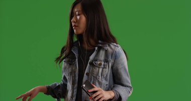 Asian female with earbuds on listening to music grooving on green screen