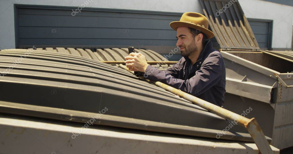 Stylish Mexican man using smartphone outdoors