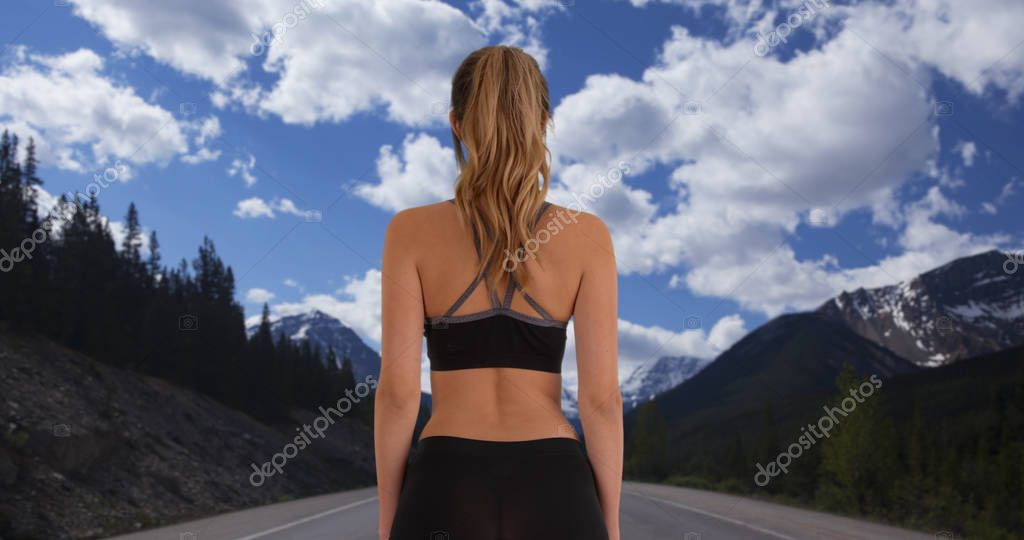 Caucasian woman shown from behind going for run on trail through the mountains