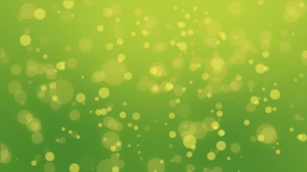 Barevné zelená žlutá částic pozadí s zářící světla v bokeh