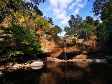 Large pool with water cascading down an over hang in Khao Yai , Thailand