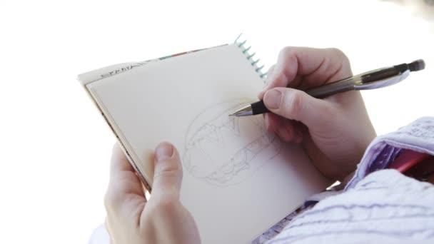 Lány művész napszemüveg felhívja a vázlatok notebook