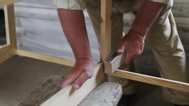 Starší muž tesař vytváří malý člun s rukama ze dřeva v malé dílně