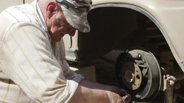 Senior man engaged in the repair of an old car