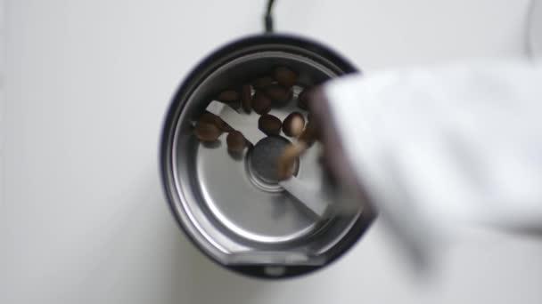 Pražená zrnková káva nalije do mlýnek na kávu
