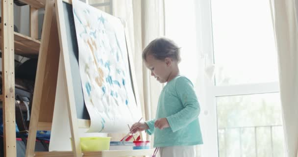 Little girl painting picture with watercolor on easel