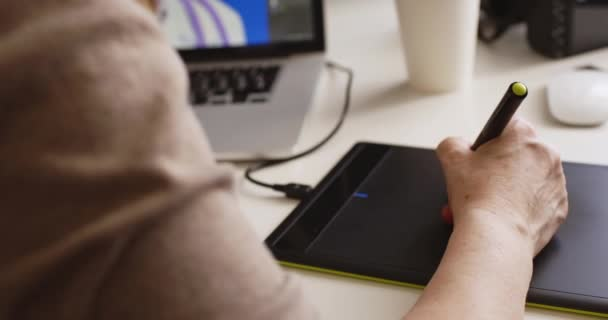 Designerin arbeitet an einem Laptop mit einem Grafik-Tablet.