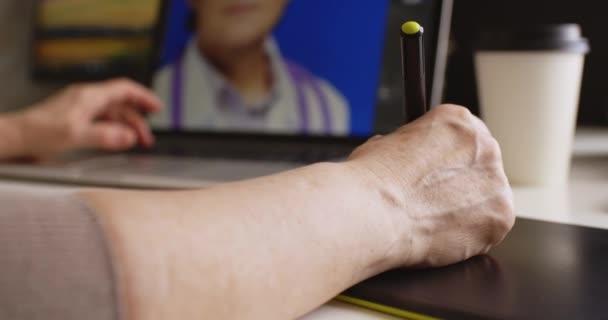 Frau-Designer arbeitet an einem Laptop mit einem Grafiktablett.