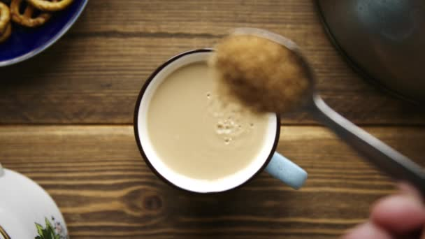 Pour cane sugar from spoon into cup of coffee with milk