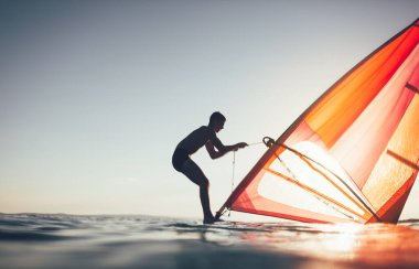 Young man uplift windsurf board sail. Surfer balancing on wind surf board on sunset sea. Windsurfing, summer, surfing, lifestyle