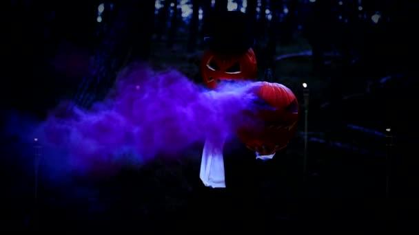 Strašidelný dýně hlavý muž drží obrovskou dýni s modrým kouřem v lese