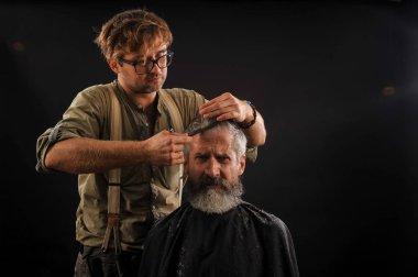 Hairdresser cuts senior citizen with a beard on a dark background
