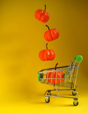 Small pumpkins fall into a grocery cart on a yellow background.