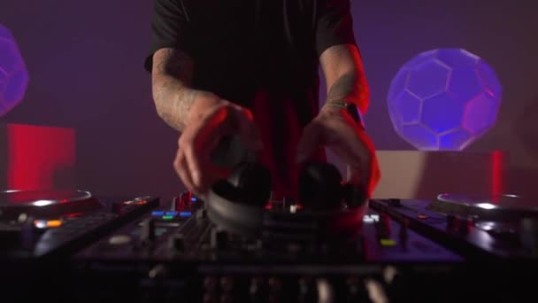 Férfi DJ fülhallgatót tesz fel sötét lila hangulatú háttérben. Disc zsoké felkészülés.