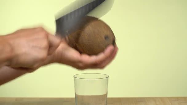 Kavkazské ruce tloukly do kokosu velkým nožem, aby ho otevřely a vytáhly z něj šťávu. Kapalina vstupuje do sklenice. Barvené pozadí studia.