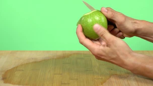 Oloupni zelené jablko. Kavkazské ruce oloupají malé nožem zelené jablko. Zelené pozadí studia.