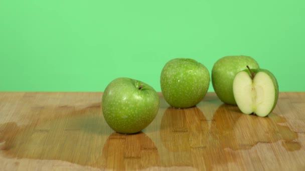 Kavkazské ruce ukazují nůž a dělají rychlý a čistý řez v polovině zeleného jablka. Zelené pozadí studia.