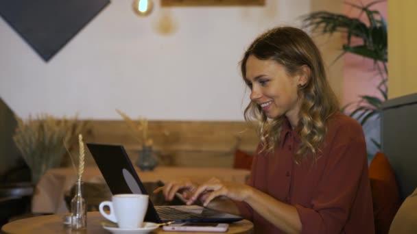 Mosolygó női szabadúszó laptoppal dolgozik egy kávézóban. Vonzó üzletasszony, aki produktív az irodán kívül. A kezek gyorsan gépelnek.
