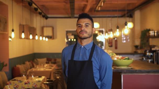 Vážně sebevědomý pohledný obchodník se zkříženýma rukama na prsou a stojí v jídelně moderní restaurace. Africký americký číšník dívá na kameru s odhodláním.