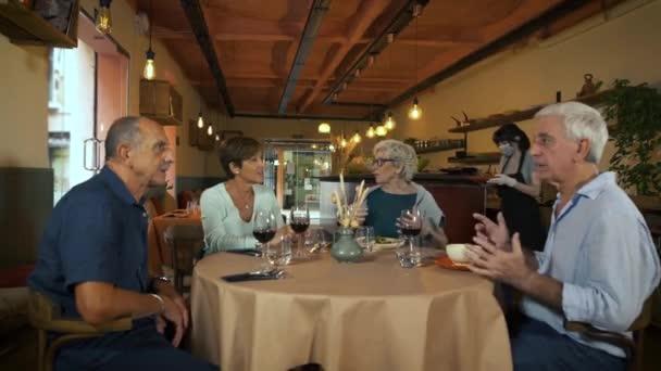 Mladá servírka s chirurgickou obličejovou maskou a rukavicemi, servíruje talíře na jídelníčku skupině seniorů sedících v restauraci. Přátelé ve výslužbě spolu tráví čas během pandemie koronaviru.