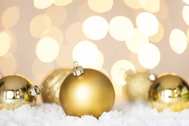 Golden Christmas baubles on snow, tree lights background