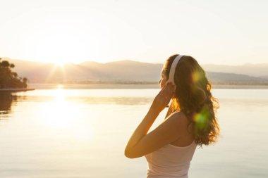 Woman in headphones enjoying sunrise over the sea stock vector