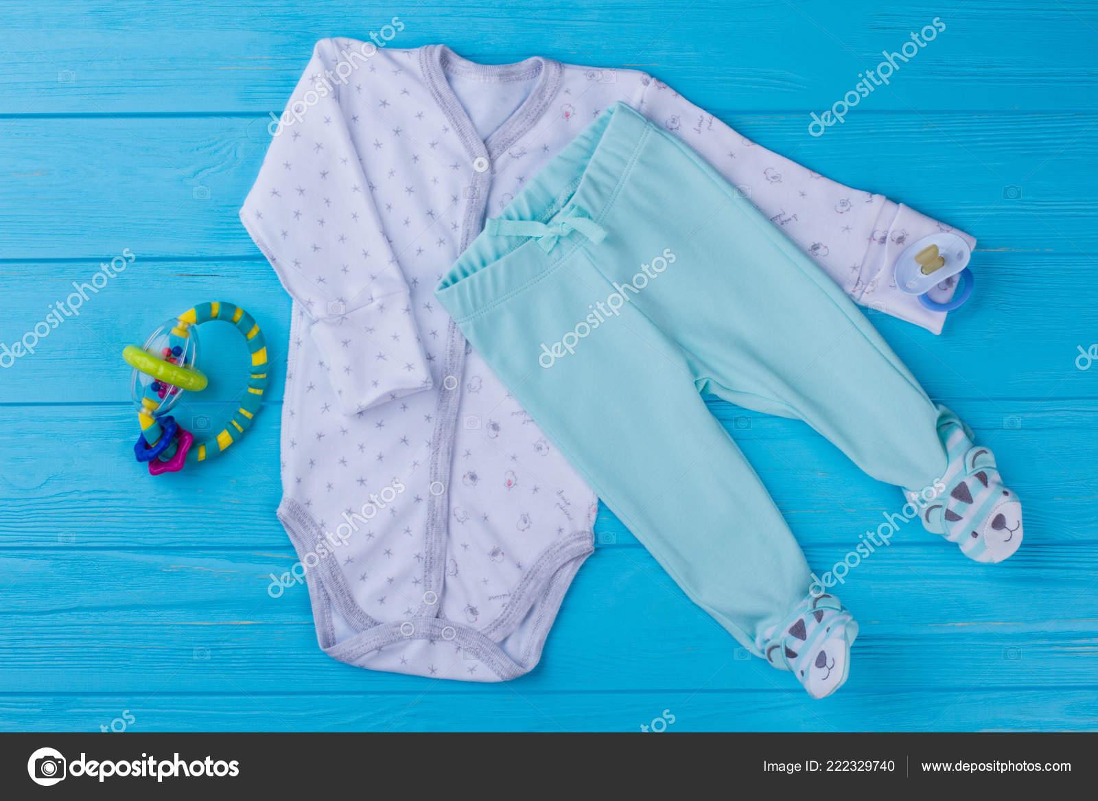 b04d1518f4a0 Bebé pijama sonajero juguete y. Enterizo de niño blanco y pantalones patas  divertidos. Fondo de madera azul — Foto de margostock