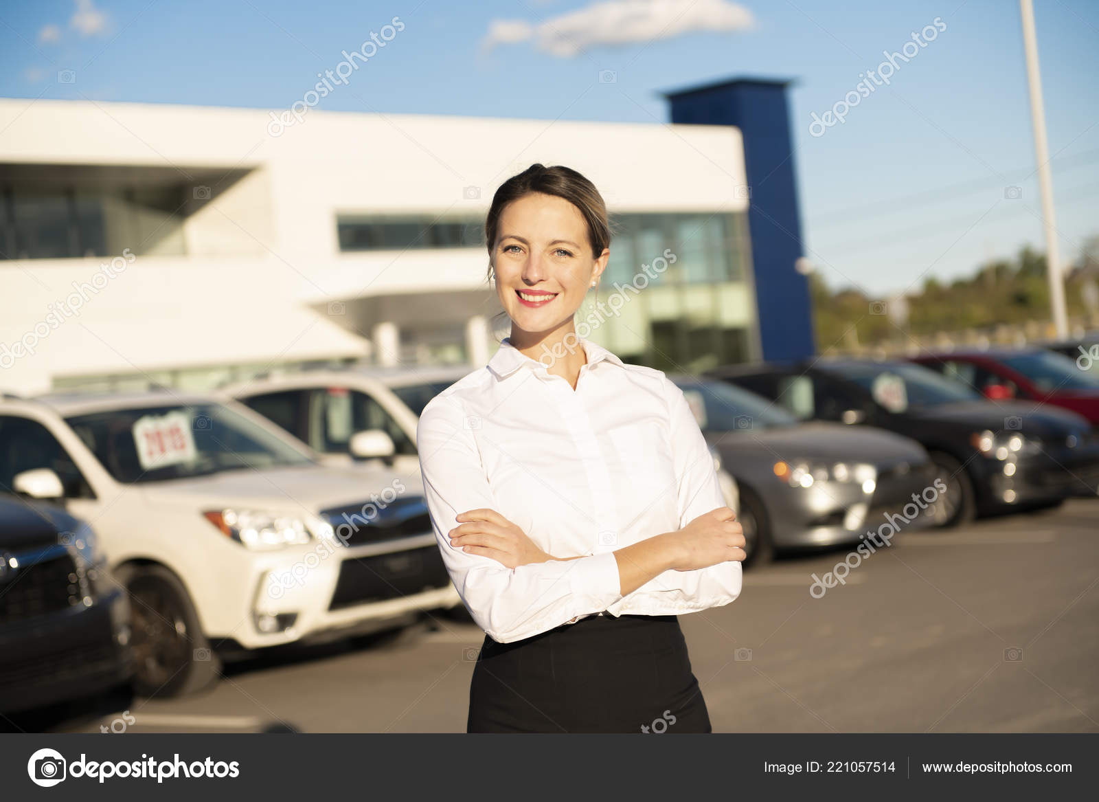 Young Woman Car Rental In Front Of Garage With Cars On The