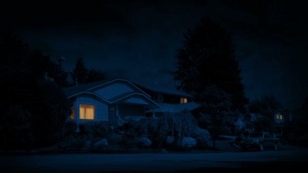 Muž chodí kolem okna rozsvícené domu na předměstí