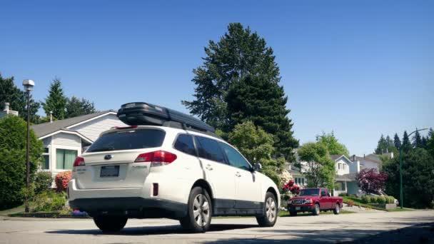 Autót vezet keresztül a külvárosokban a napsütéses napon