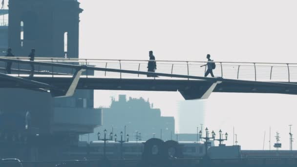 Lidé na lávce s vlaku a auta na pozadí
