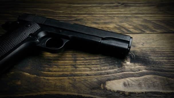 Hand Picks Up Gun Off Table Moving Shot