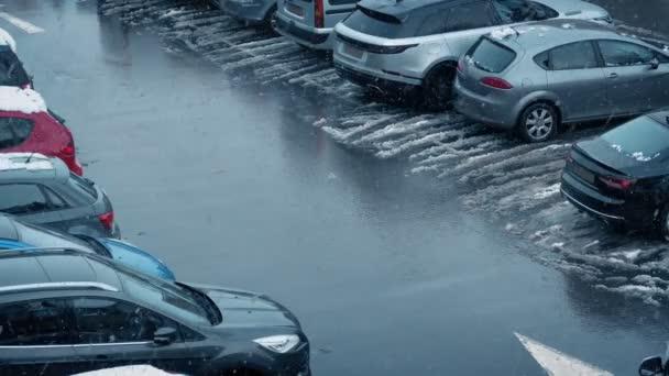 Car Drives In Car Lot During Snowfall