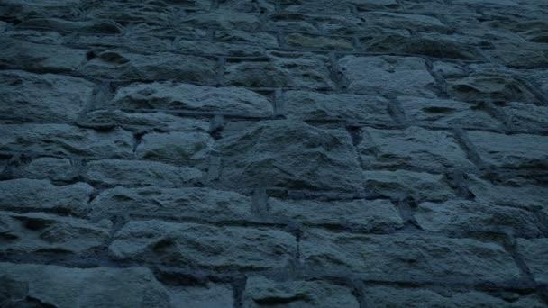Hledá se přes starou kamennou zeď ve večerních hodinách