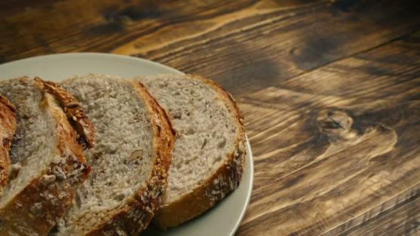 Talíř nakrájeného chleba na dřevěný stůl