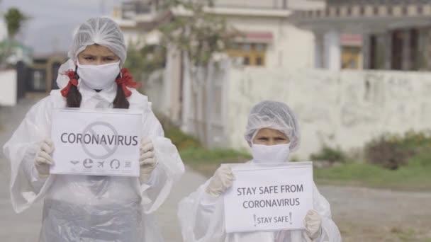 COVID-19 Coronavirus - Halálos vírus: Maszkot, kesztyűt és védőruhát viselő gyermekek iskolai egyenruhában a COVID-19 Coronavirus elleni védelem érdekében. Apple ProRes 422.Gyermekek tudatosítása