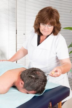 skull massage by senior woman on man patient head