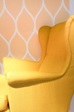 yellow armchair on background decorated in seventies atmosphere