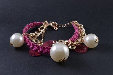 bracelet with pearls and pendants isolated on black