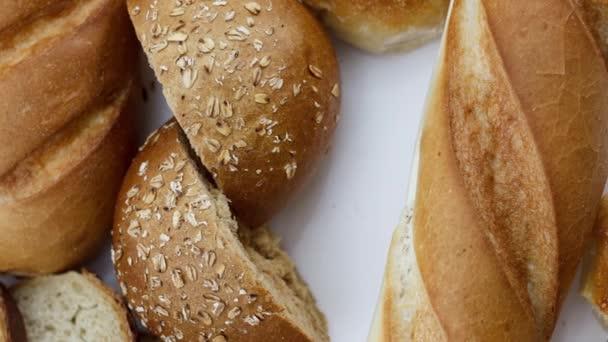 čerstvý krájený chléb a buchty na bílém stole