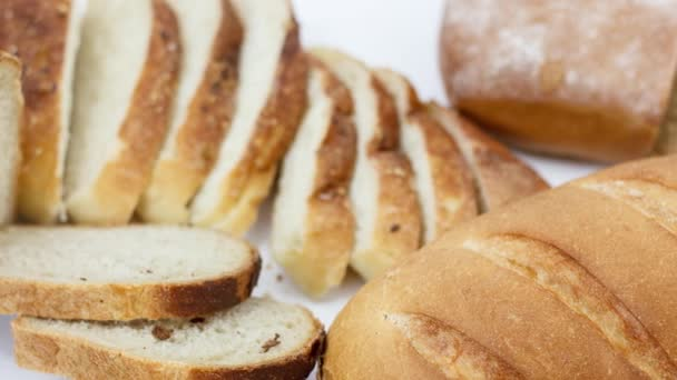 fresh sliced bread and buns on white table