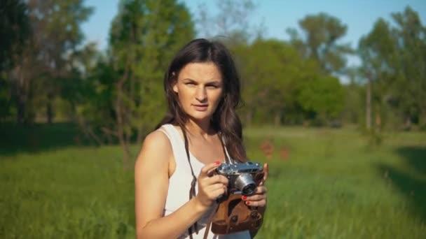 Fiatal nő fotós bevétel mozi és fénykép-val fényképezőgép a szabadban.