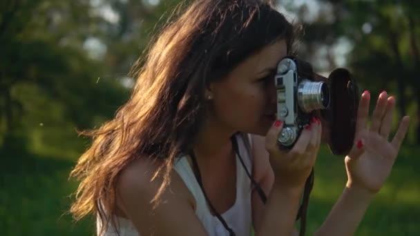 Fotografo della giovane donna che cattura immagini e foto con allaperto fotocamera.